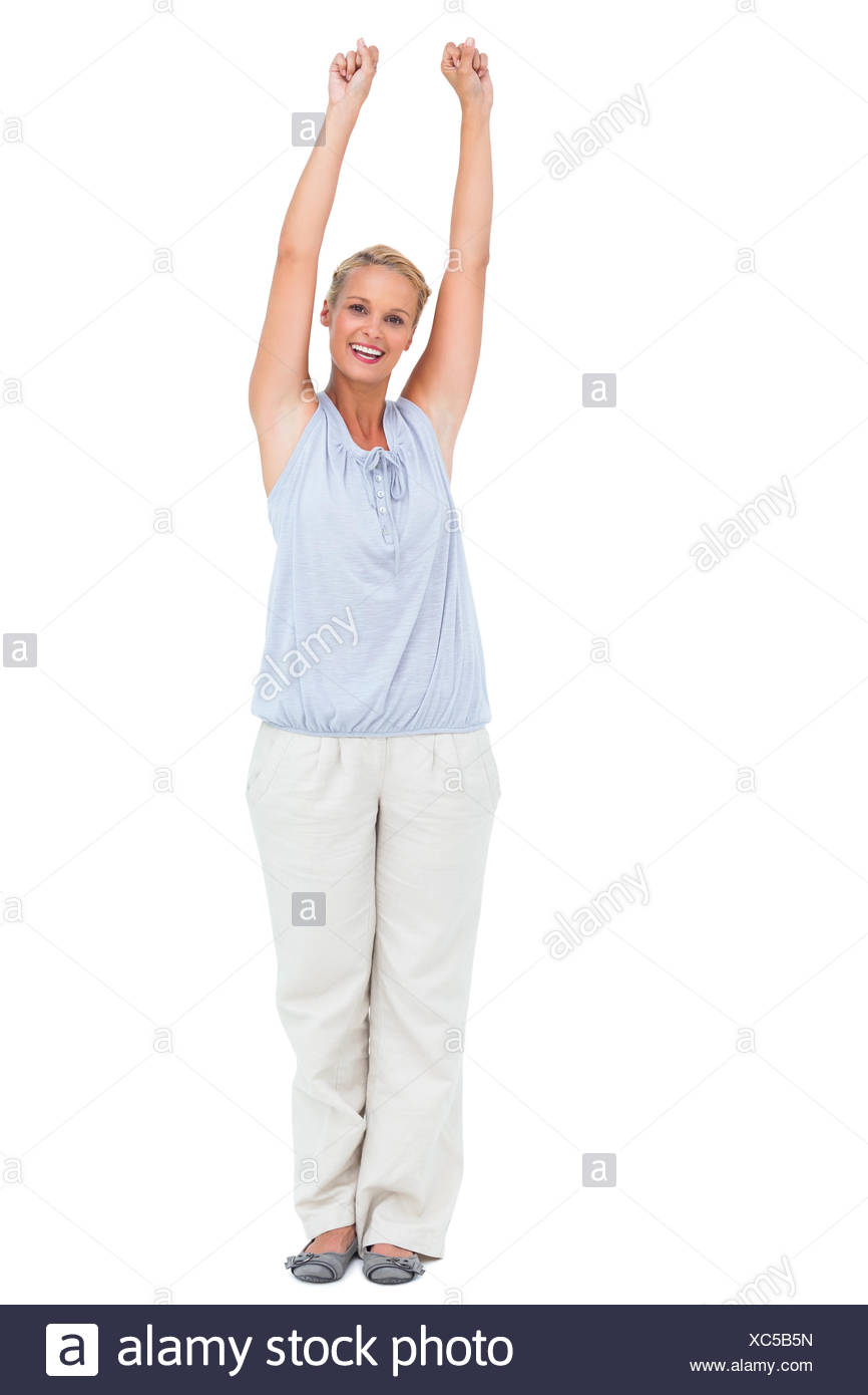 Excited woman standing with arms raised Stock Photo