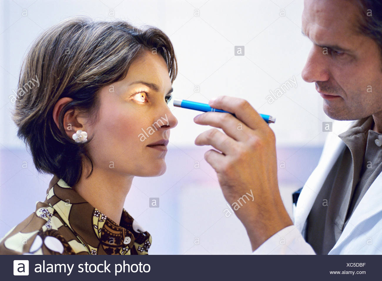 Portrait of a male doctor shining a light into a young woman's eyes - Stock Image
