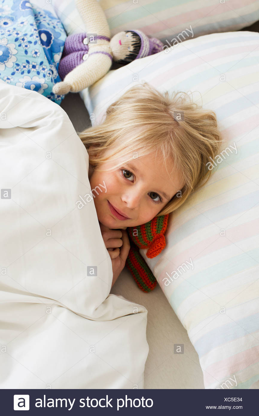 Portrait of young girl lying in bed with doll - Stock Image