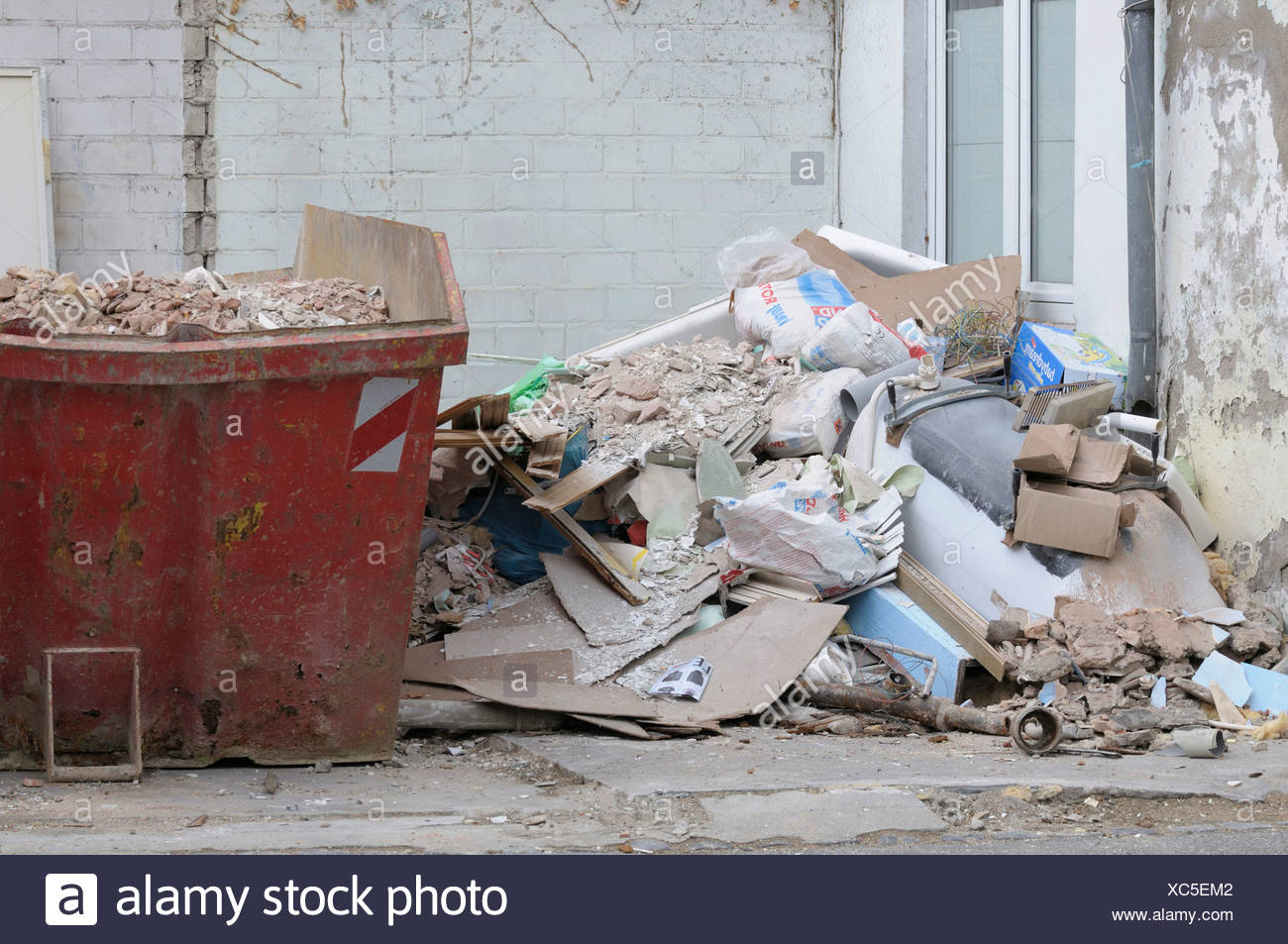 Tenement reconstruction, filled red skip, pile of debris on the side, new window at back - Stock Image