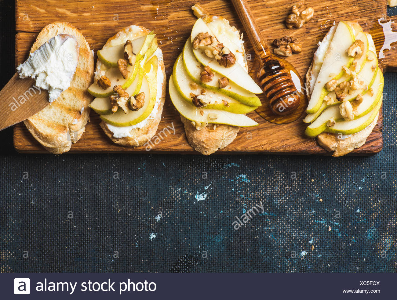 Crostini with pear, ricotta cheese, honey and walnuts. Breakfast toasts or snack sandwiches on rustic wooden board over dark blu - Stock Image