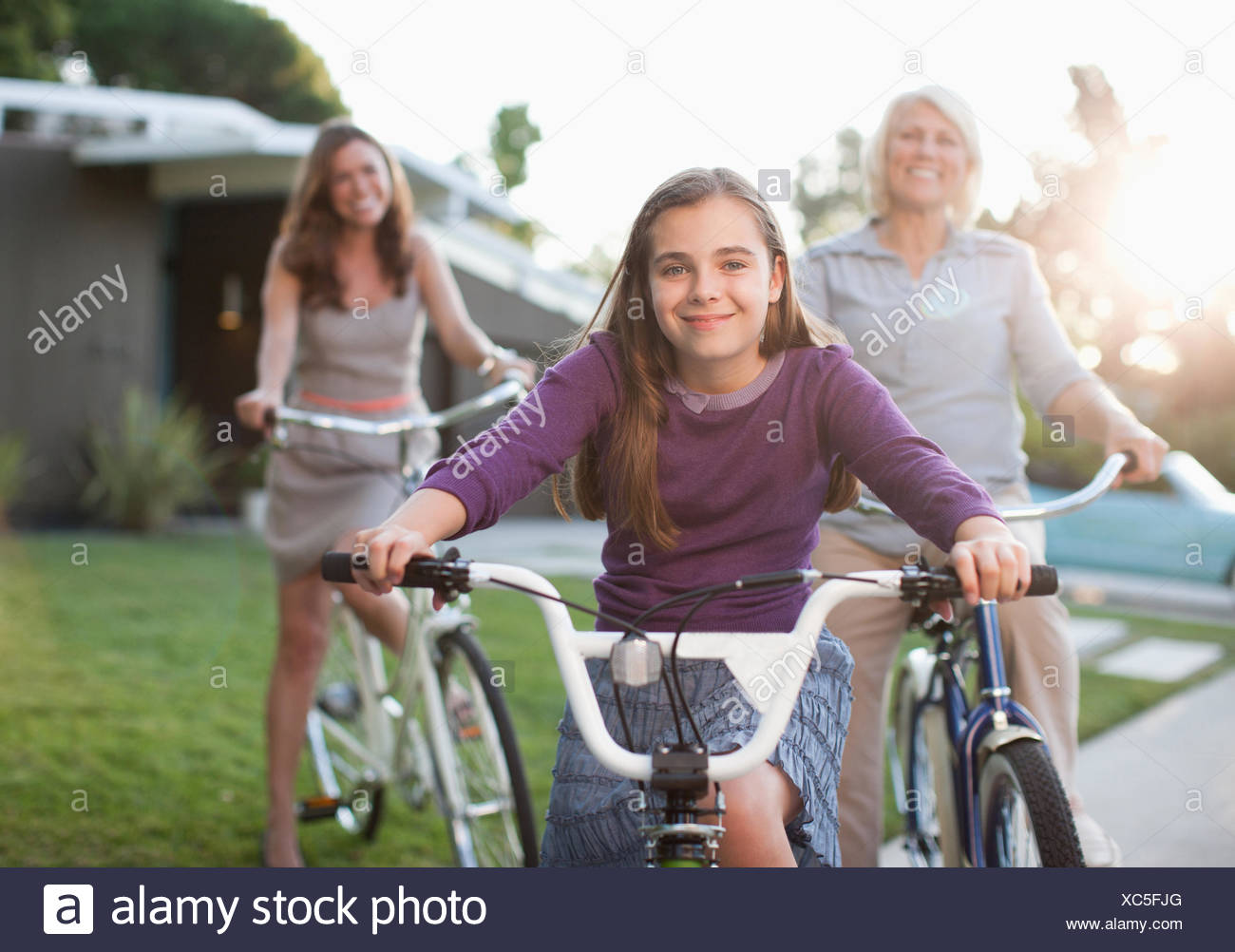 Three generations of women riding bicycles - Stock Image