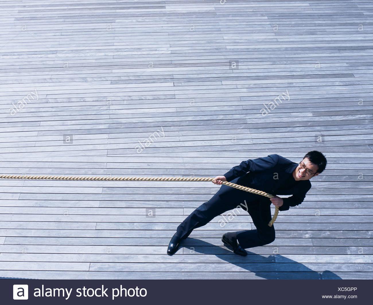 Asian Man pulling at a rope - Stock Image