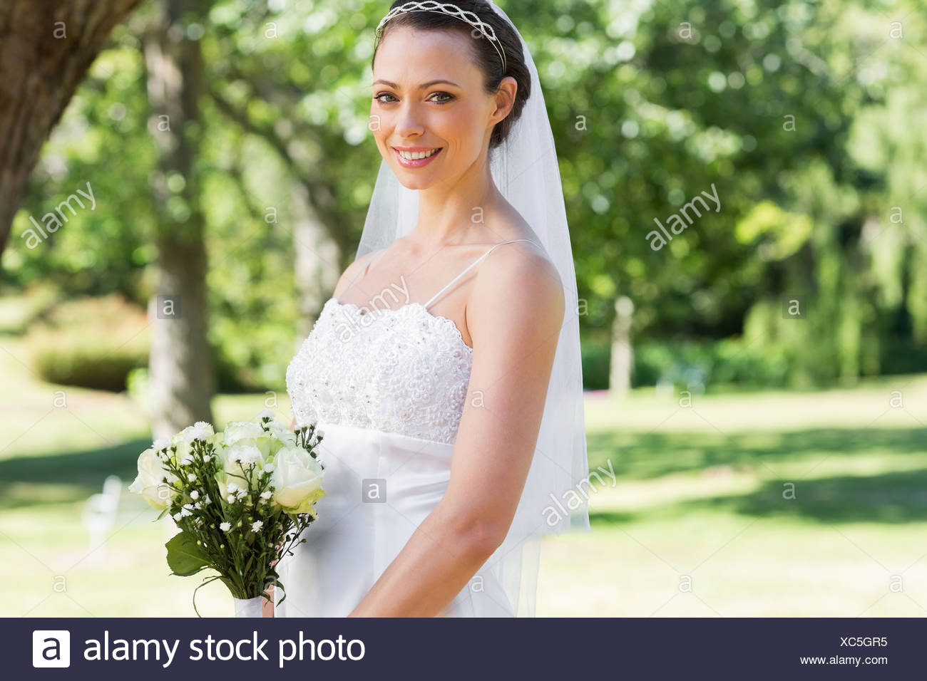 Bride with flower bouquet in garden - Stock Image