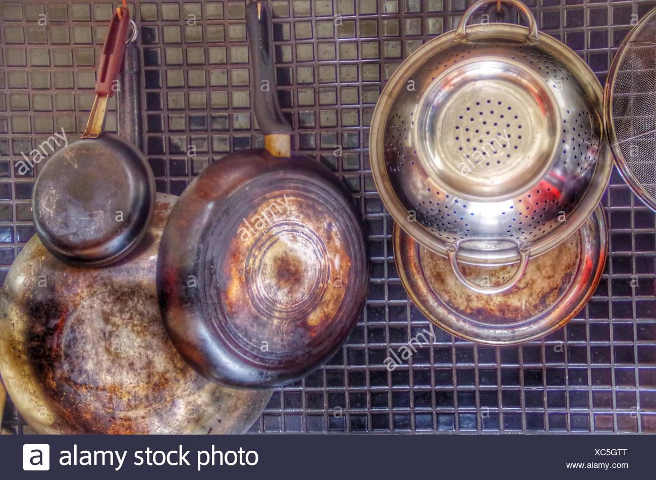 Saucepans And Kitchen Utensils Hanging On Backsplash At Home - Stock Image
