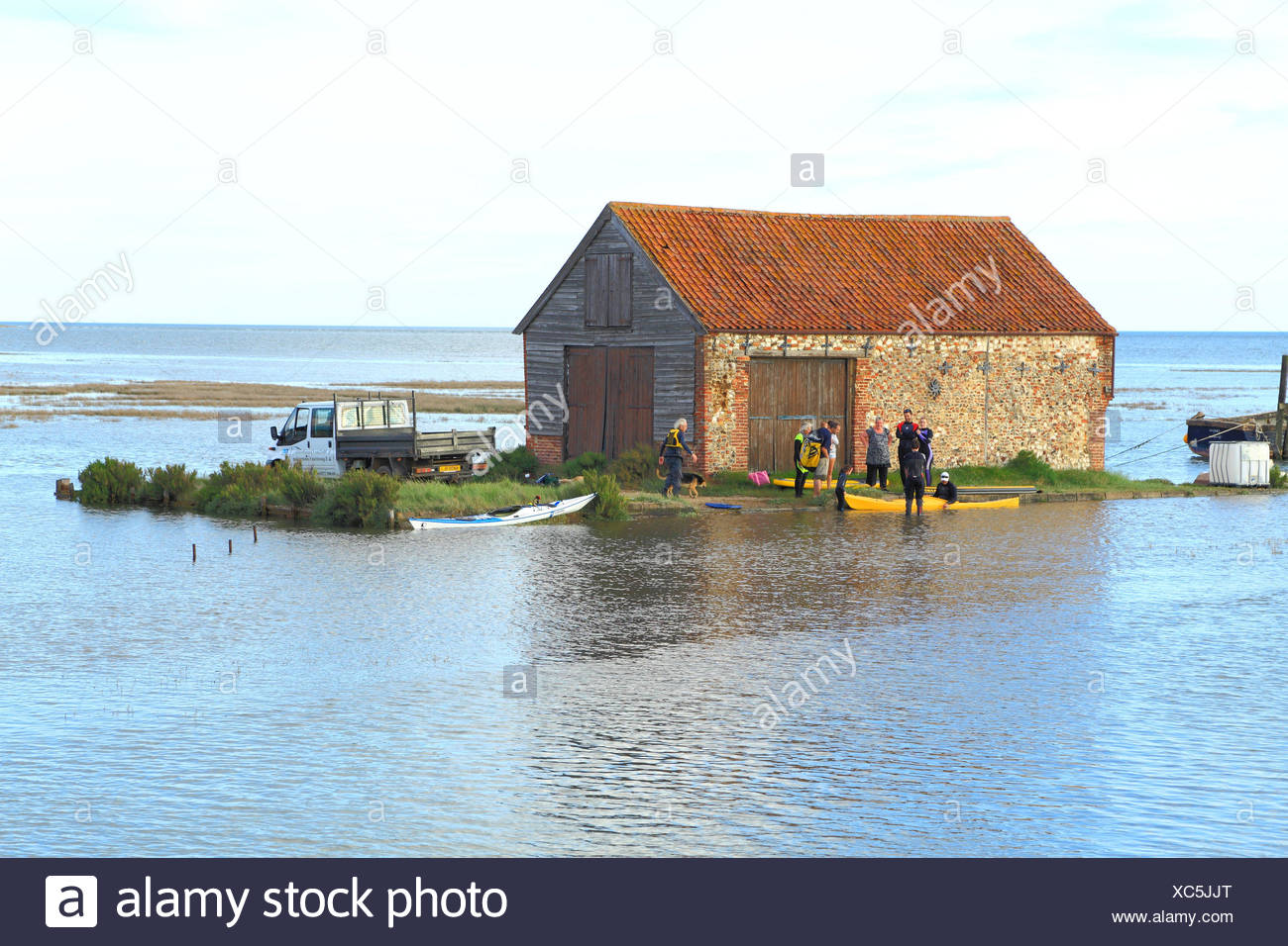 Truck, vehicle, people, cut off by high tide, North Sea surge, Coal Barn, Thornham, Norfolk, England, UK - Stock Image