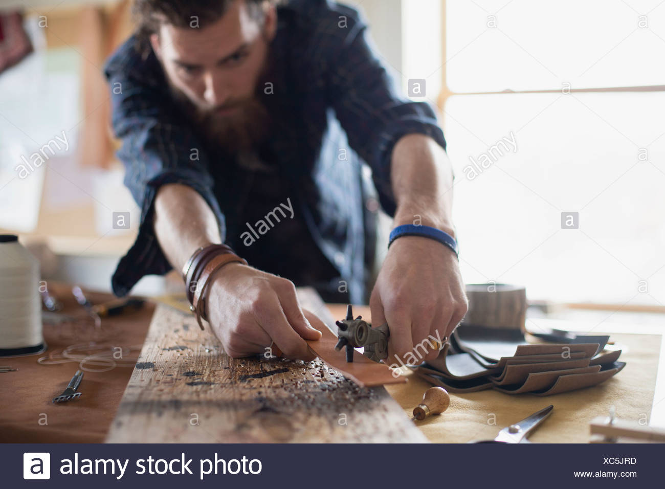 Man punching holes in leather belt at table Stock Photo
