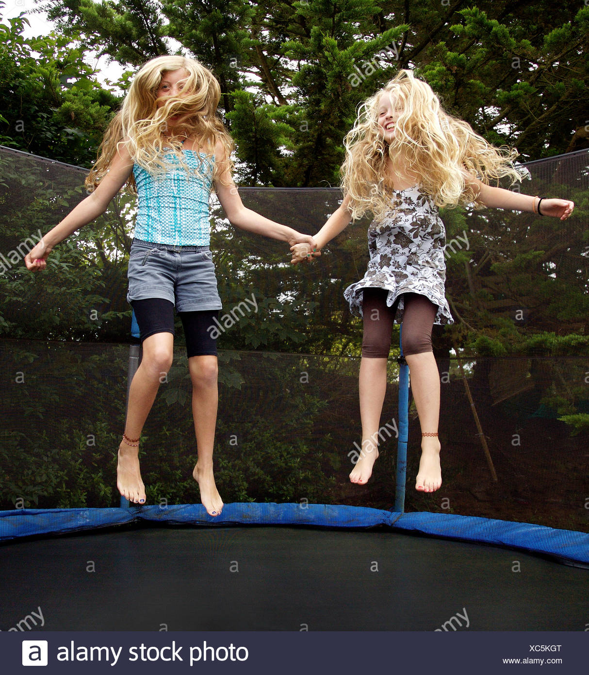 Girls jumping on trampoline outdoors Stock Photo