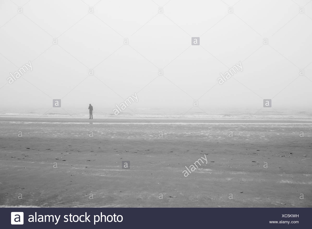 1 single person alone on the beach of the North Sea, - Stock Image