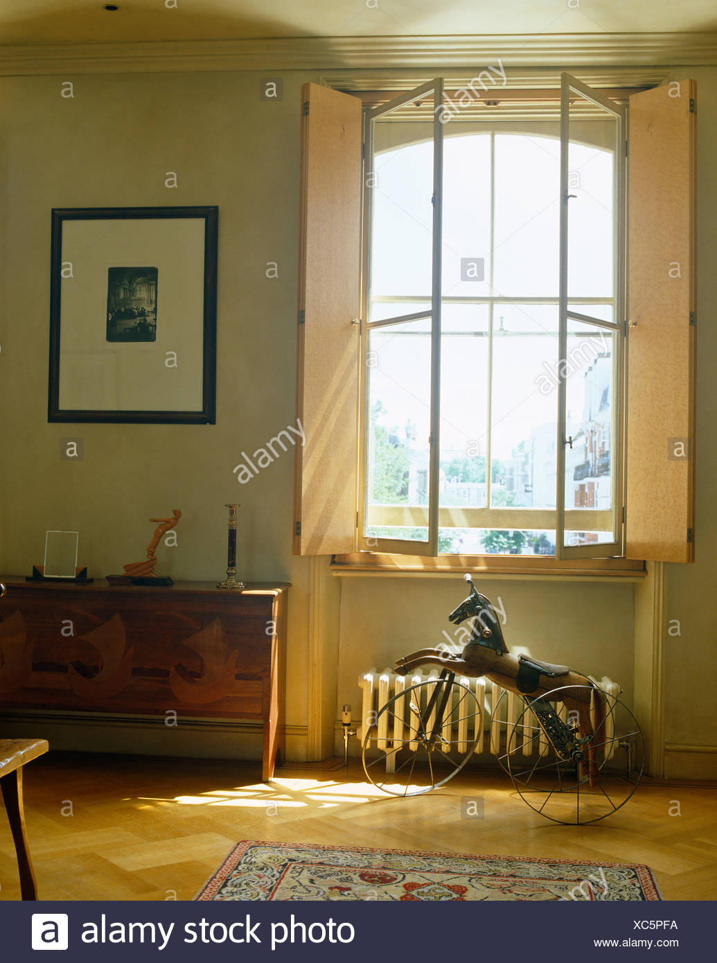 Shutters on tall window above bicycle wheeled metal horse in modern bedroom Stock Photo