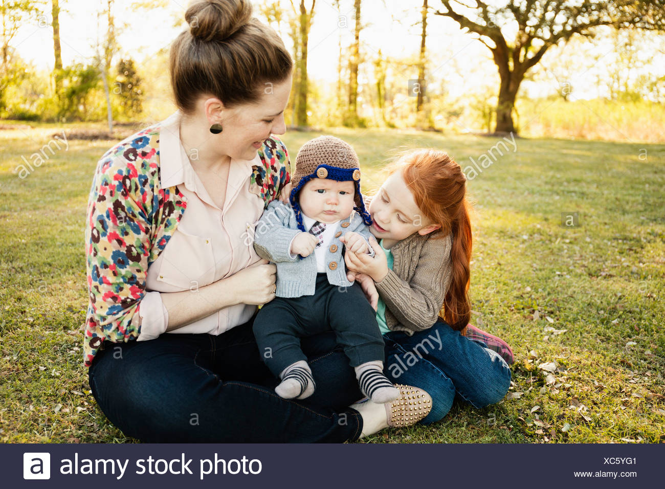 Mid adult mother, daughter and baby son in park - Stock Image