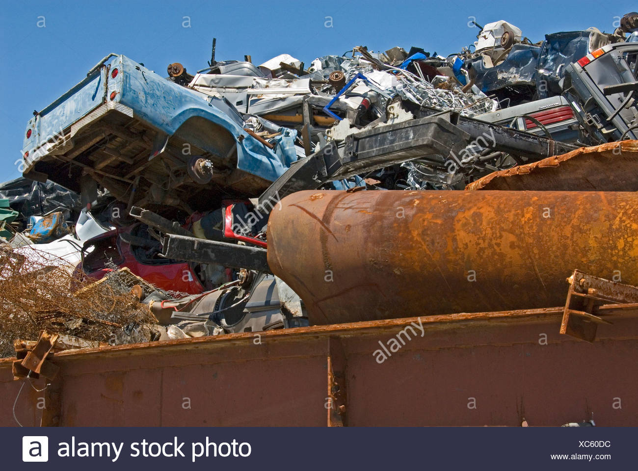 Looking up at a scrap metal dump with a wrecked car sticking