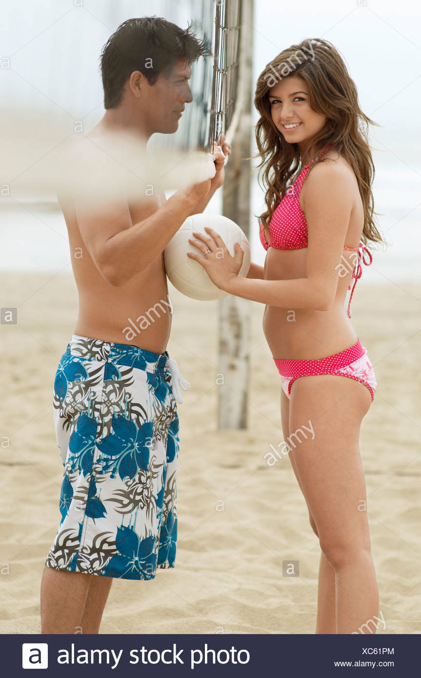 Couple Flirting on Beach with volleyball net between them, woman holding ball against her boyfriend - Stock Image