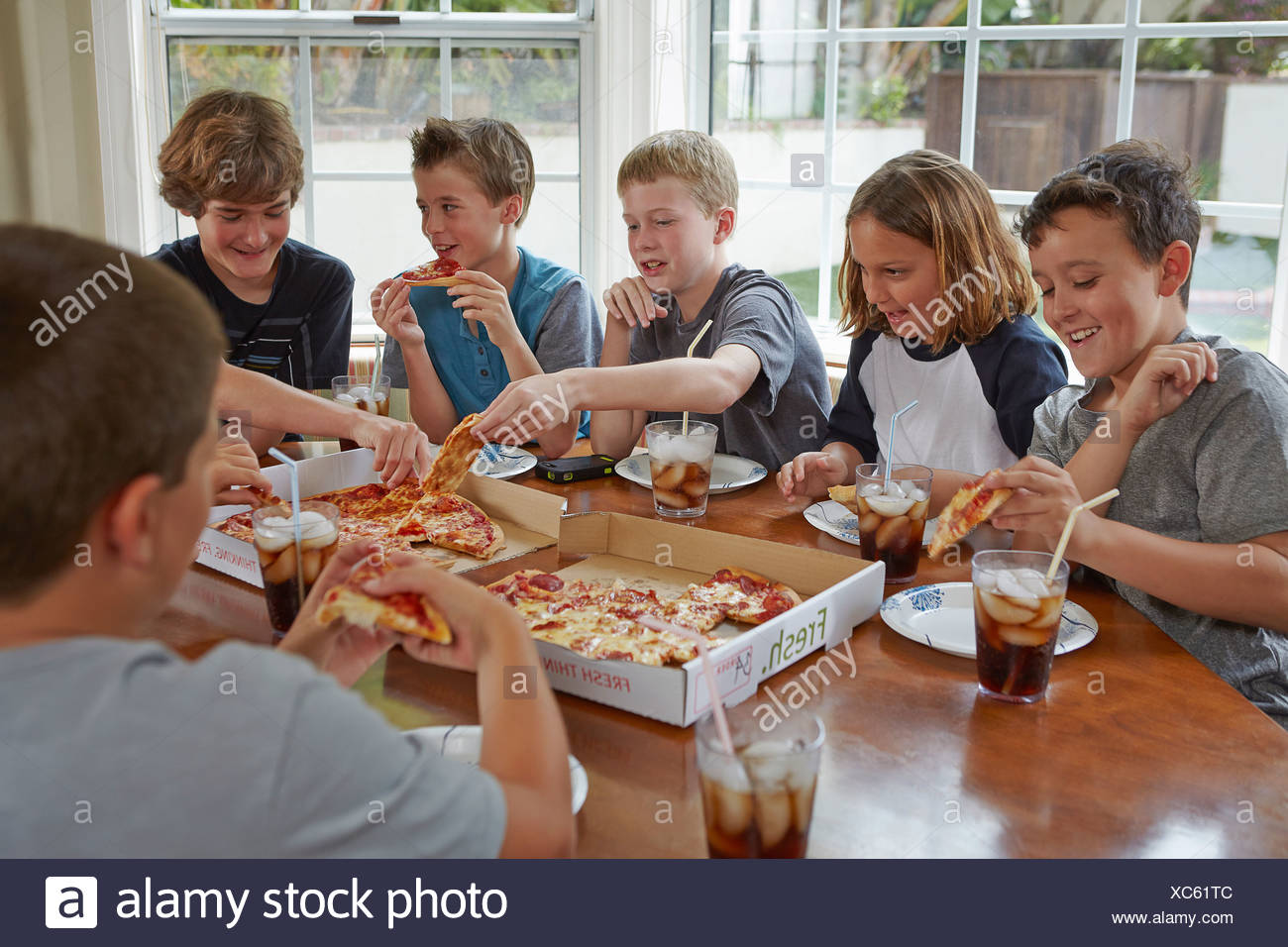 Group of boys sharing pizza - Stock Image