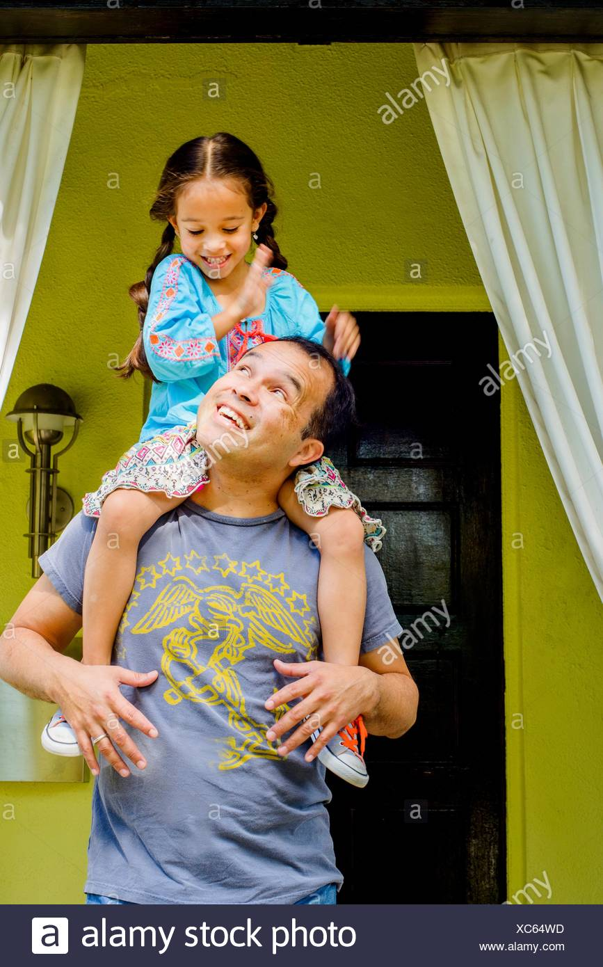 Girl getting a shoulder carry from father in garden porch - Stock Image