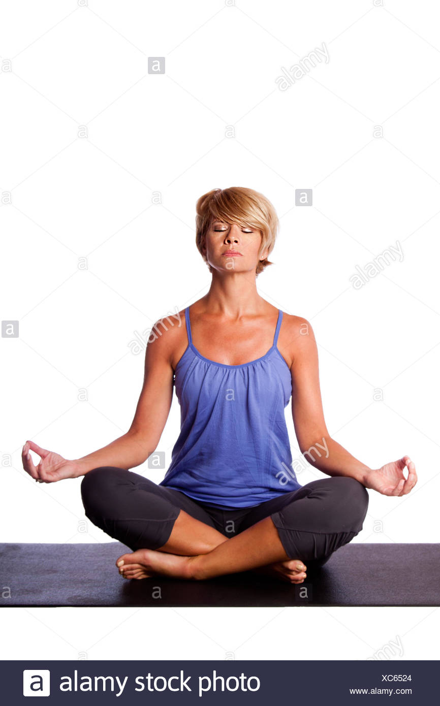 Beautiful woman in Gentle Seated Lotus Position, Padmasana, in yoga meditation to align chakra, on white. Stock Photo