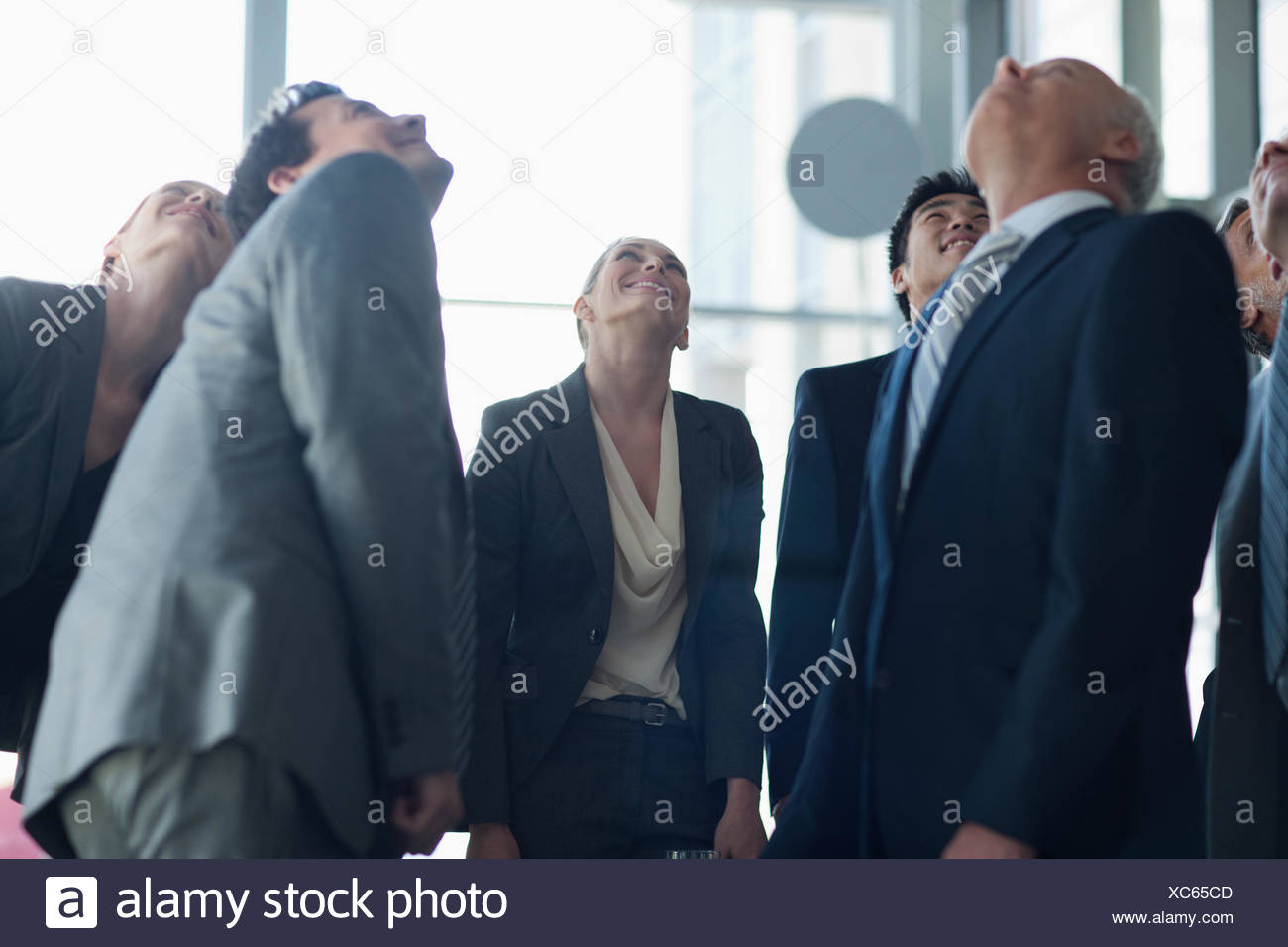 Business people looking up in lobby - Stock Image