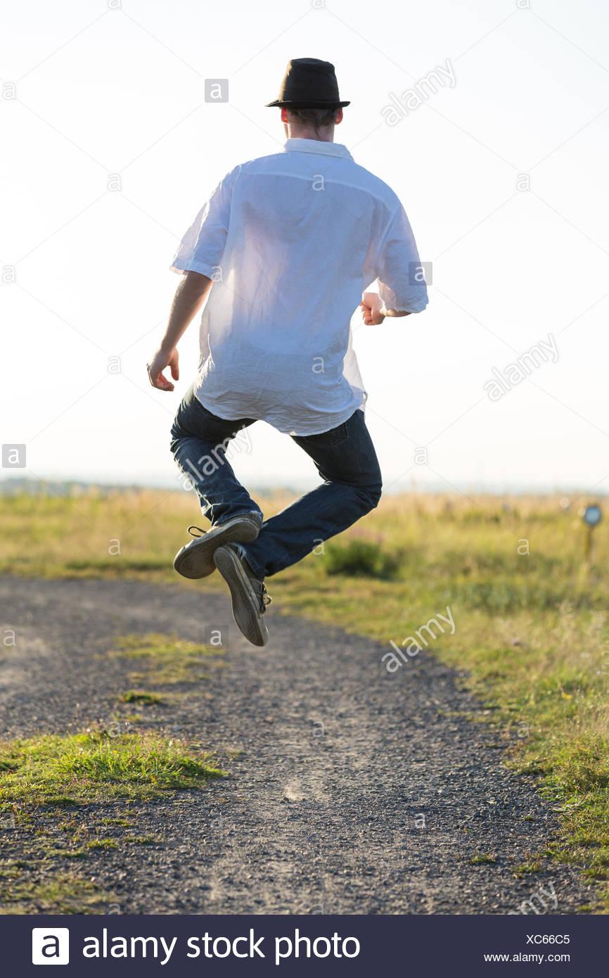 walk go going walking dust field spring bouncing bounces hop skipping frisks jumping jump bizarre business dealings deal - Stock Image