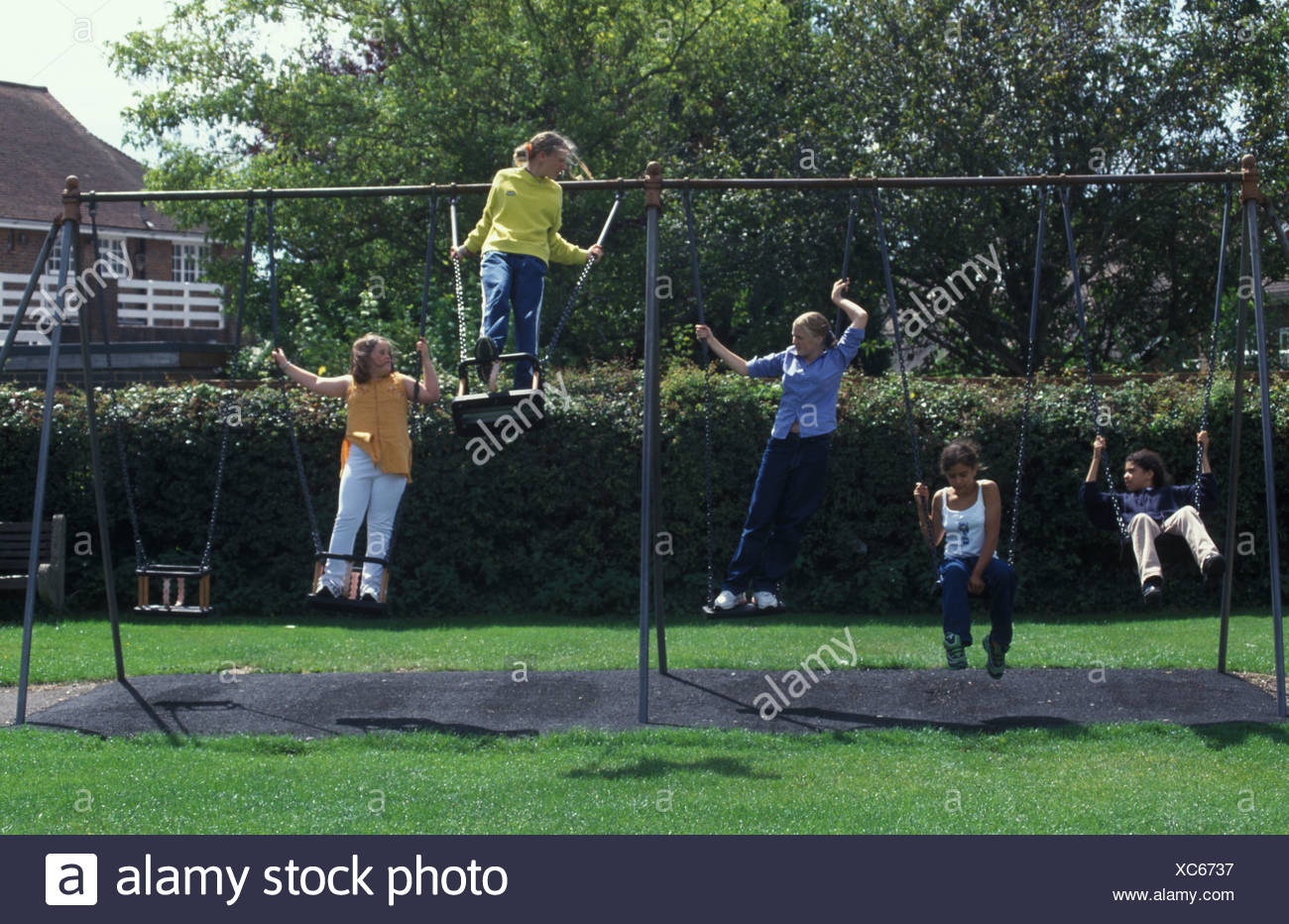 teenagers on swings in the local park - Stock Image