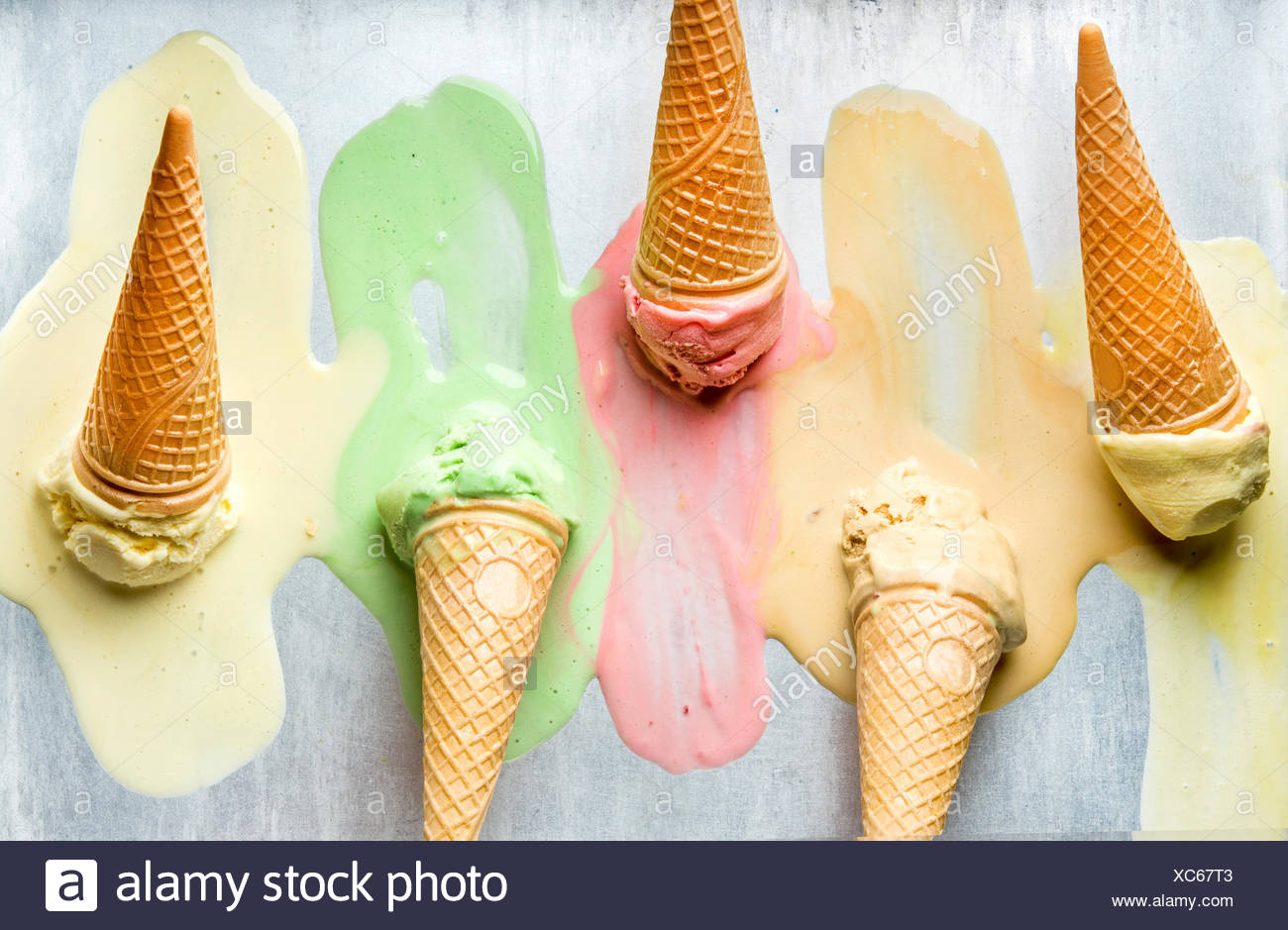 Colorful ice cream cones of different flavors. Melting scoops. Top view, steel metal background Stock Photo