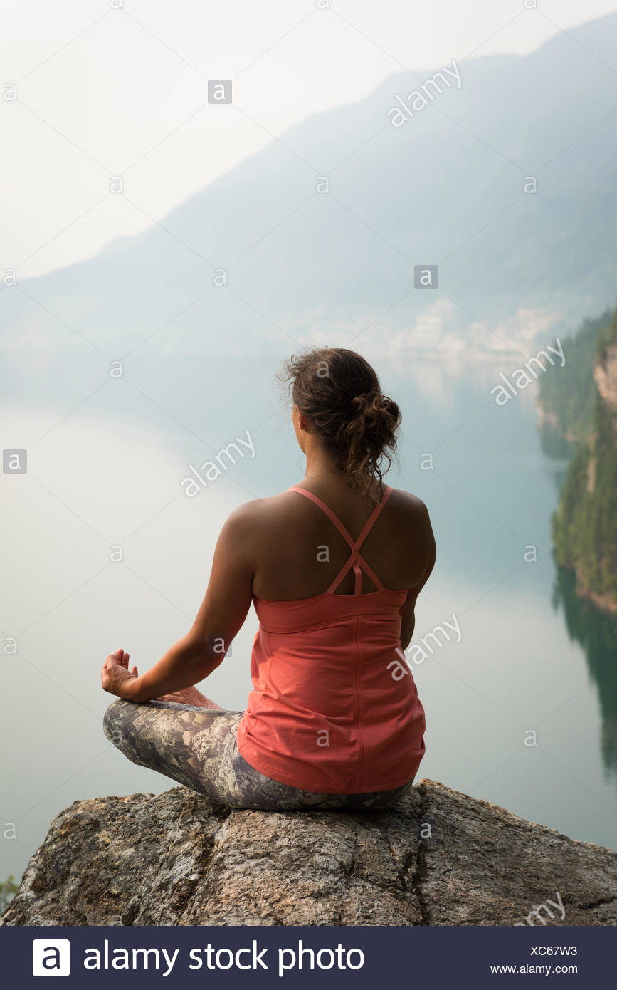 Fit woman sitting in meditating posture on the edge of a rock - Stock Image