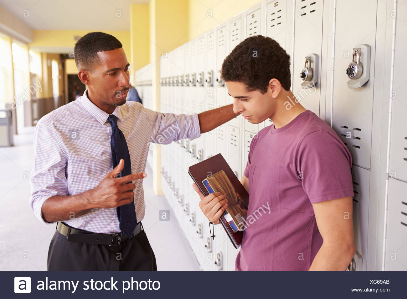 Male High School Student Talking To Teacher By Lockers - Stock Image