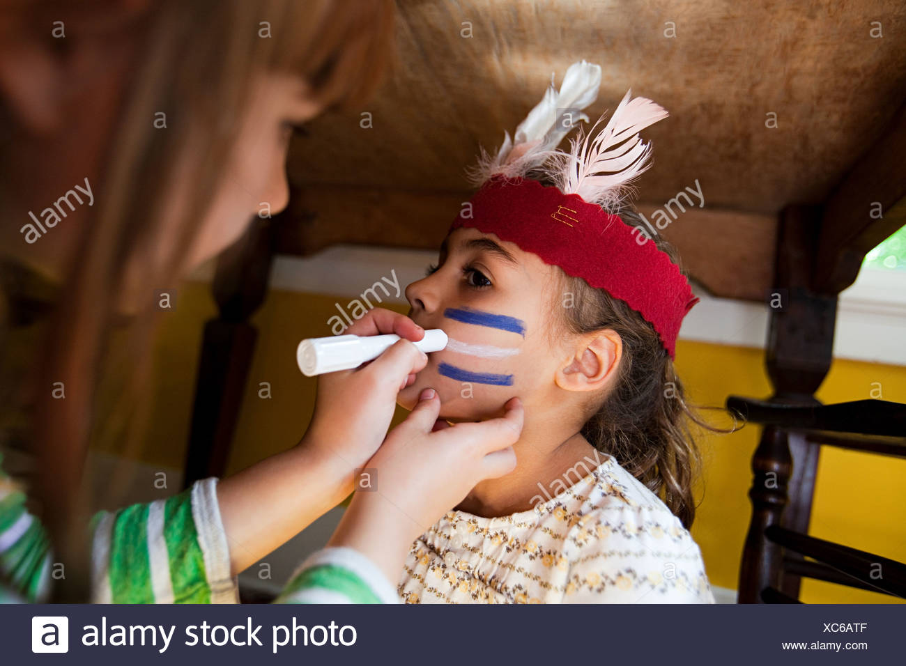 Girl putting Native American face paint on another girl - Stock Image