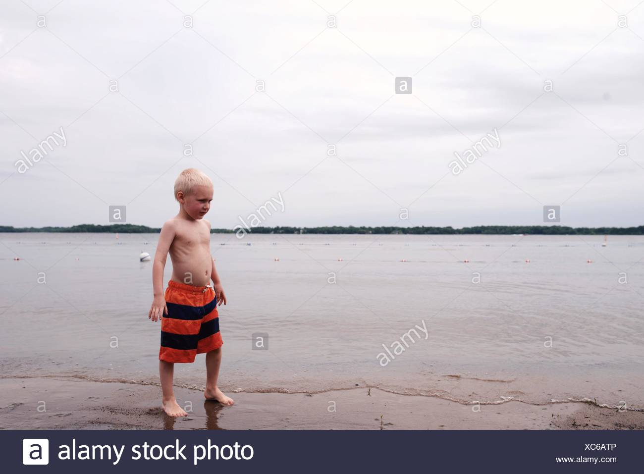 Boy Standing On Sea Shore Against Sky - Stock Image