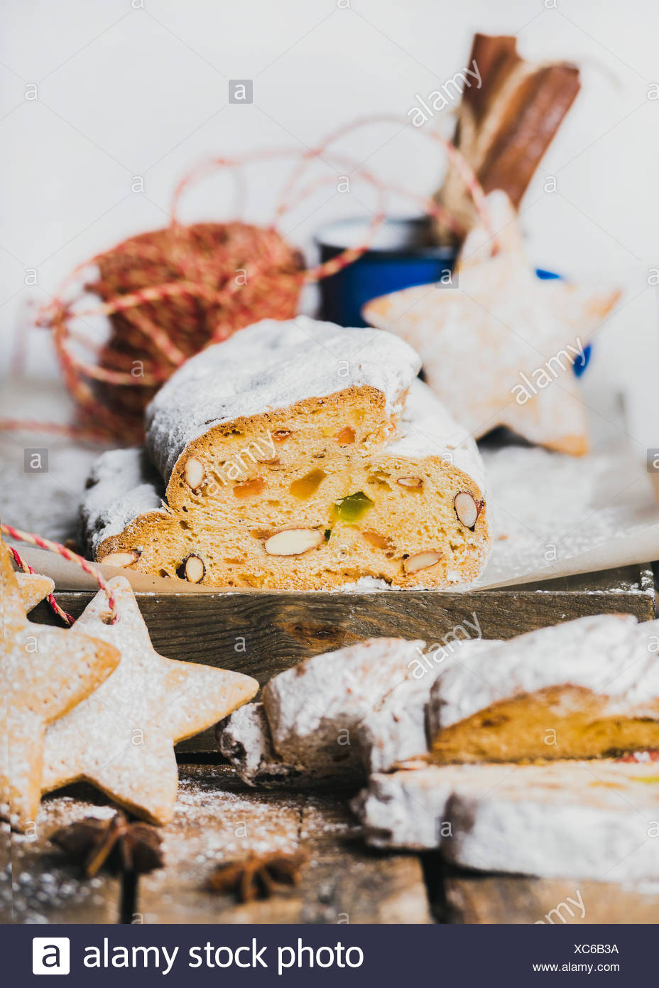 Piece of Traditional German Christmas cake Stollen with festive gingerbread star shaped cookies, selective focus, white background, vertical compositi - Stock Image