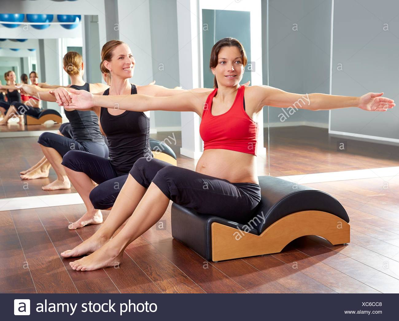 pregnant woman pilates exercise spine twist with Wave corrector and personal trainer. - Stock Image