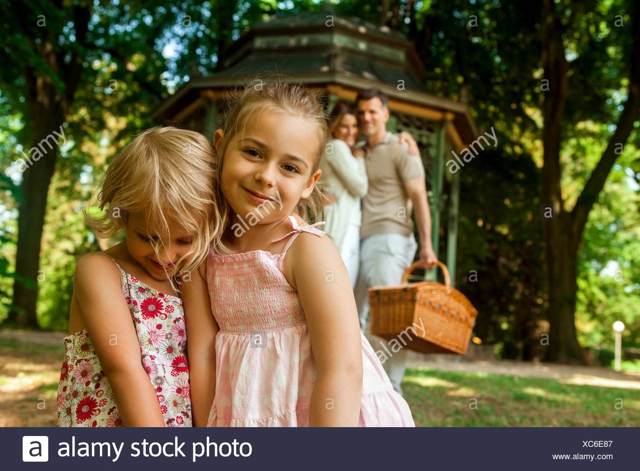Happy family in park parents carrying picnic basket - Stock Image
