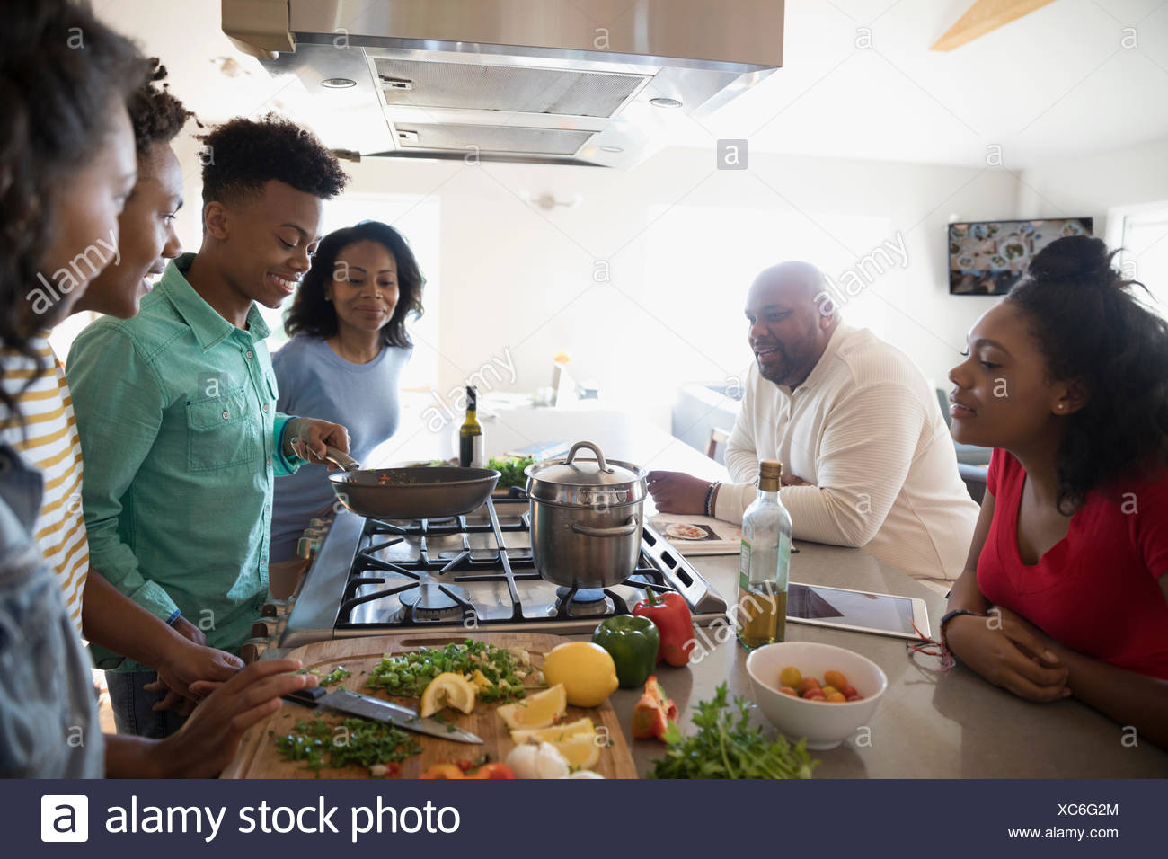 African American family cooking in kitchen - Stock Image