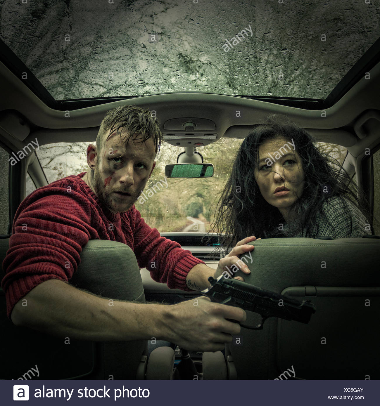 Man and woman in car with handgun Stock Photo