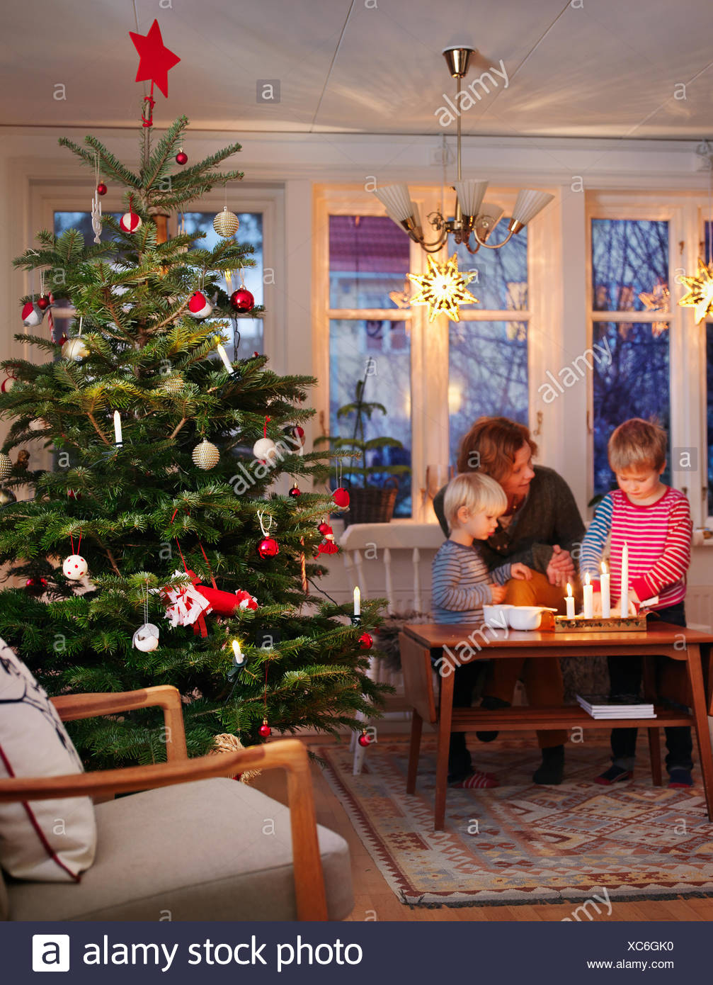 Woman and boys at table by christmas tree - Stock Image