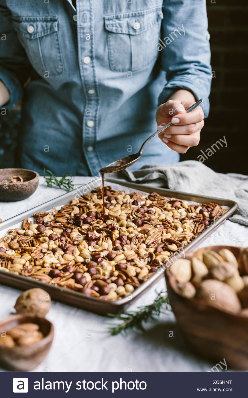A woman is photographed from the front view as she is drizzling a sheet of mixed nuts with spicy simple syrup. - Stock Image