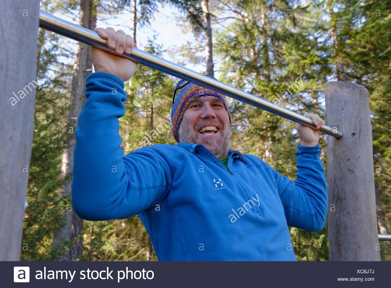 Man doing pull-ups on a bar, Naturschauspiel Kreuth, adventure trail along the Weissach, Weissach near Kreuth, Upper Bavaria - Stock Image