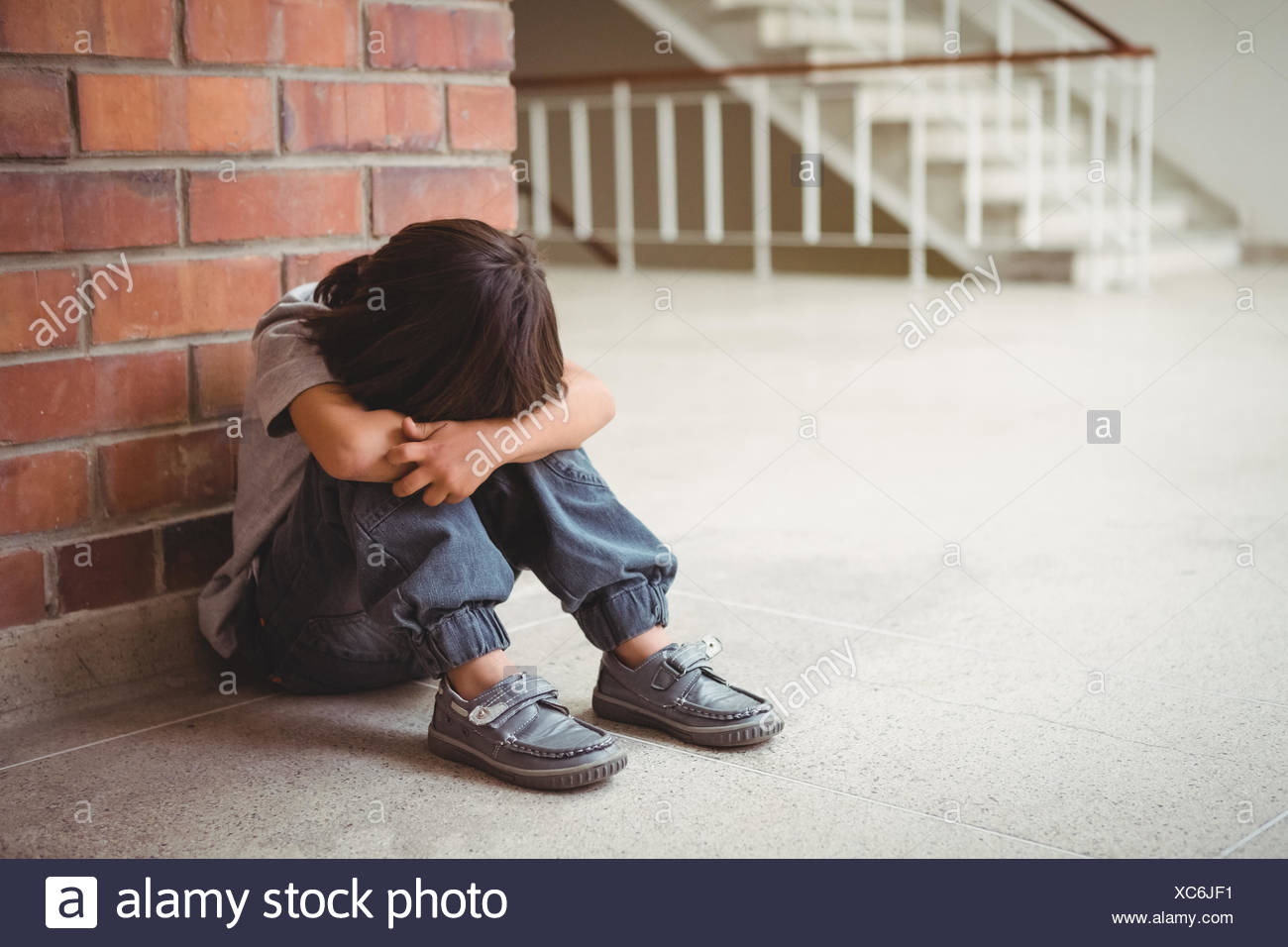 Upset lonely child sitting by himself - Stock Image