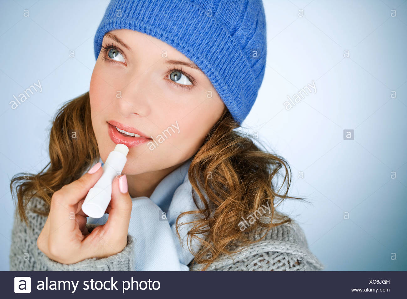 A young woman applying lip balm, in wintertime - Stock Image