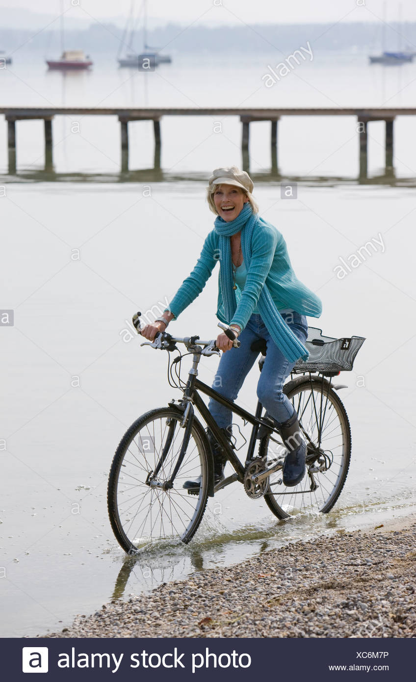 A senior woman riding a bicycle along the shore of a lake - Stock Image