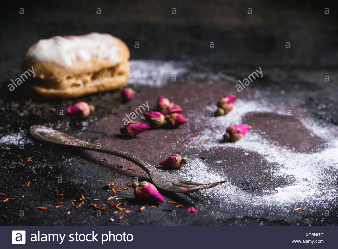 Eclairs and trace of the eclair in sugar powder, with dry tea rose buds and vintage cutlery over dark background - Stock Image