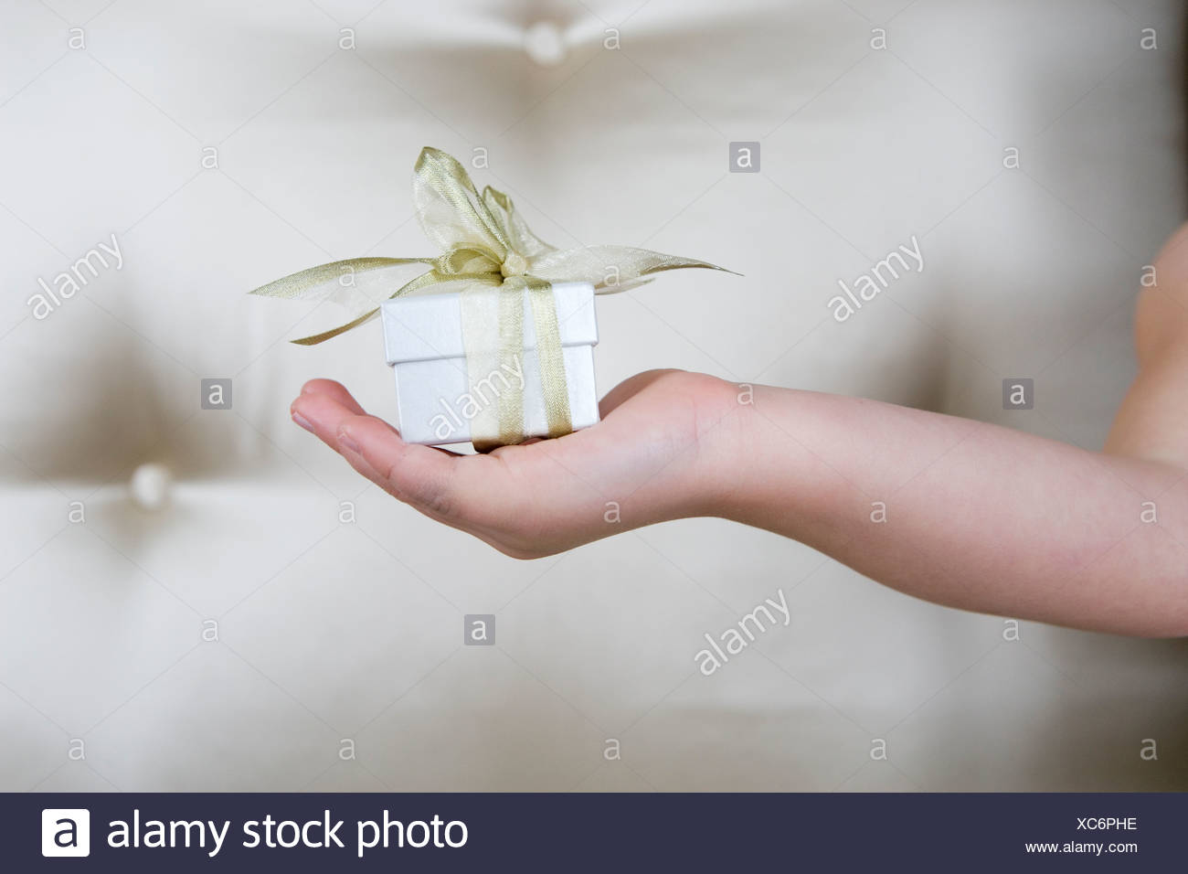Little girl holding a present, close up - Stock Image
