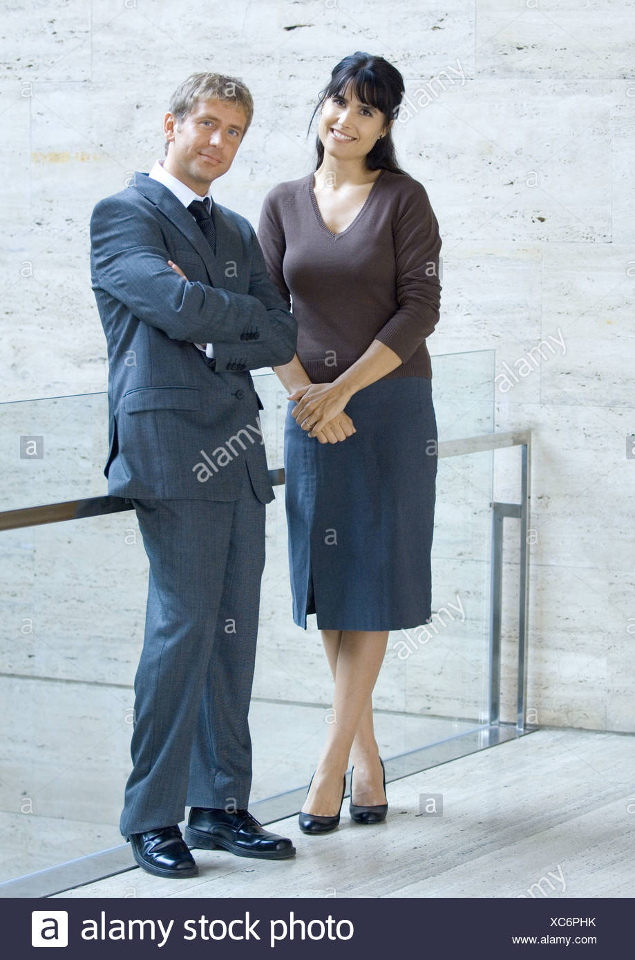 Businessman and woman, standing and smiling, portrait - Stock Image