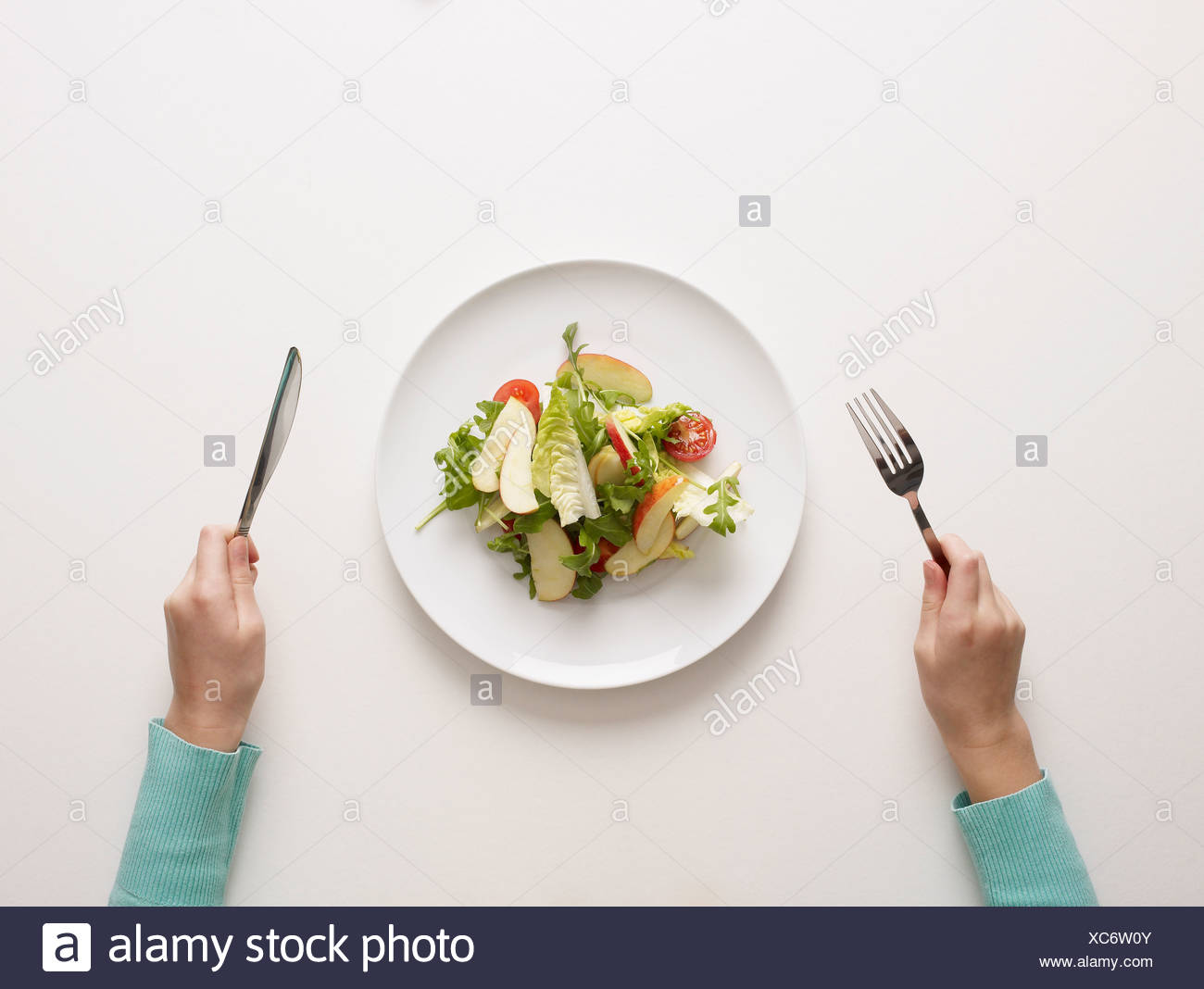 Hands by a plate of salad - Stock Image