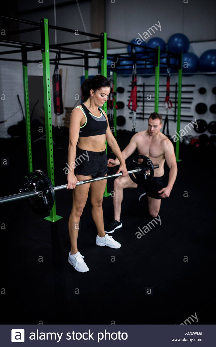 Trainer instructing a woman while lifting barbell - Stock Image