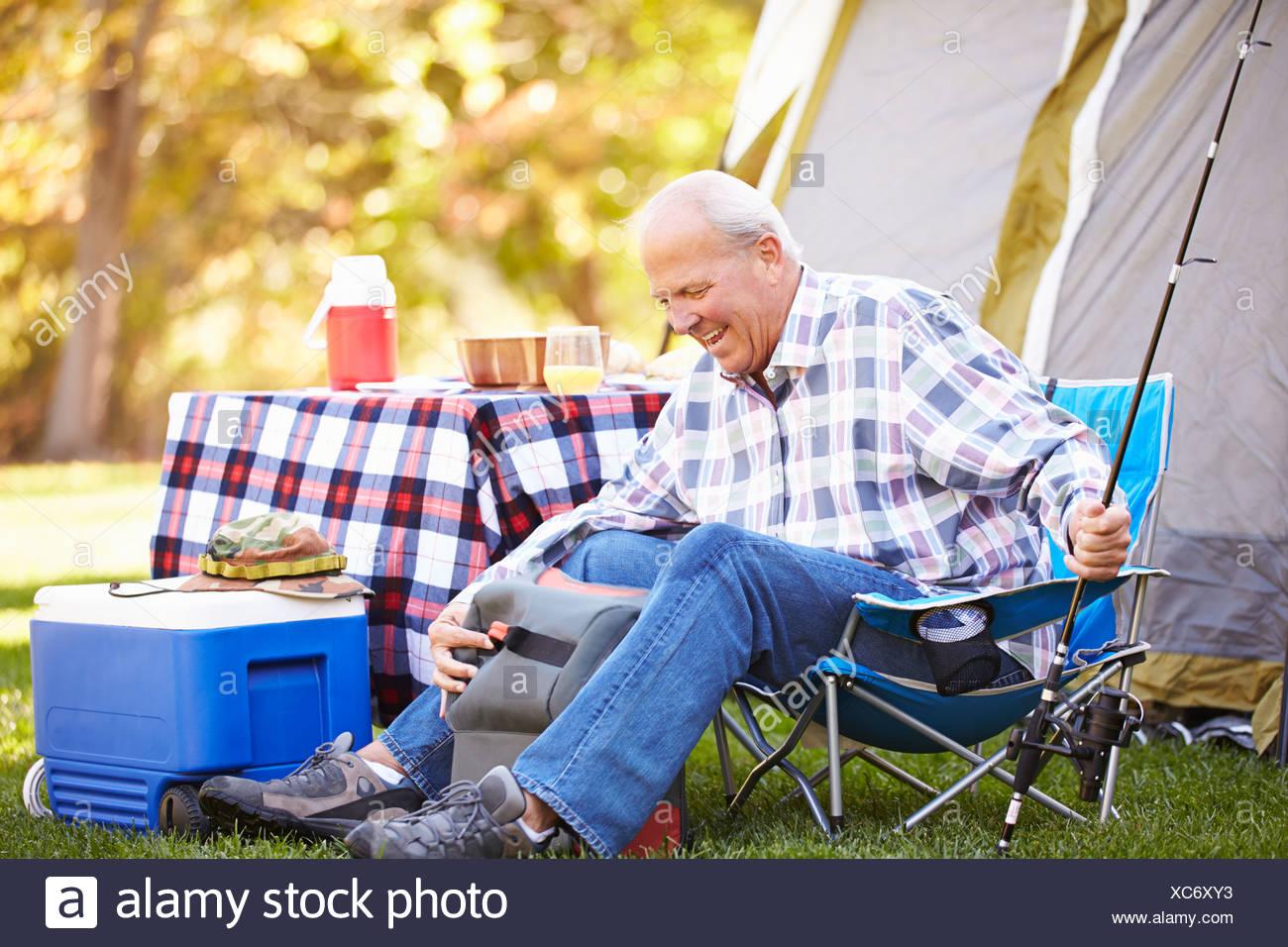 Senior Man On Camping Holiday With Fishing Rod - Stock Image