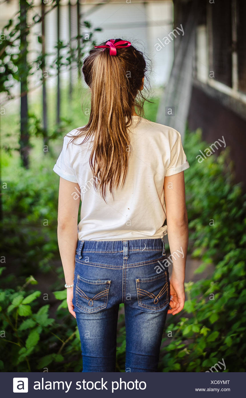 Rear view of a girl standing in a garden - Stock Image