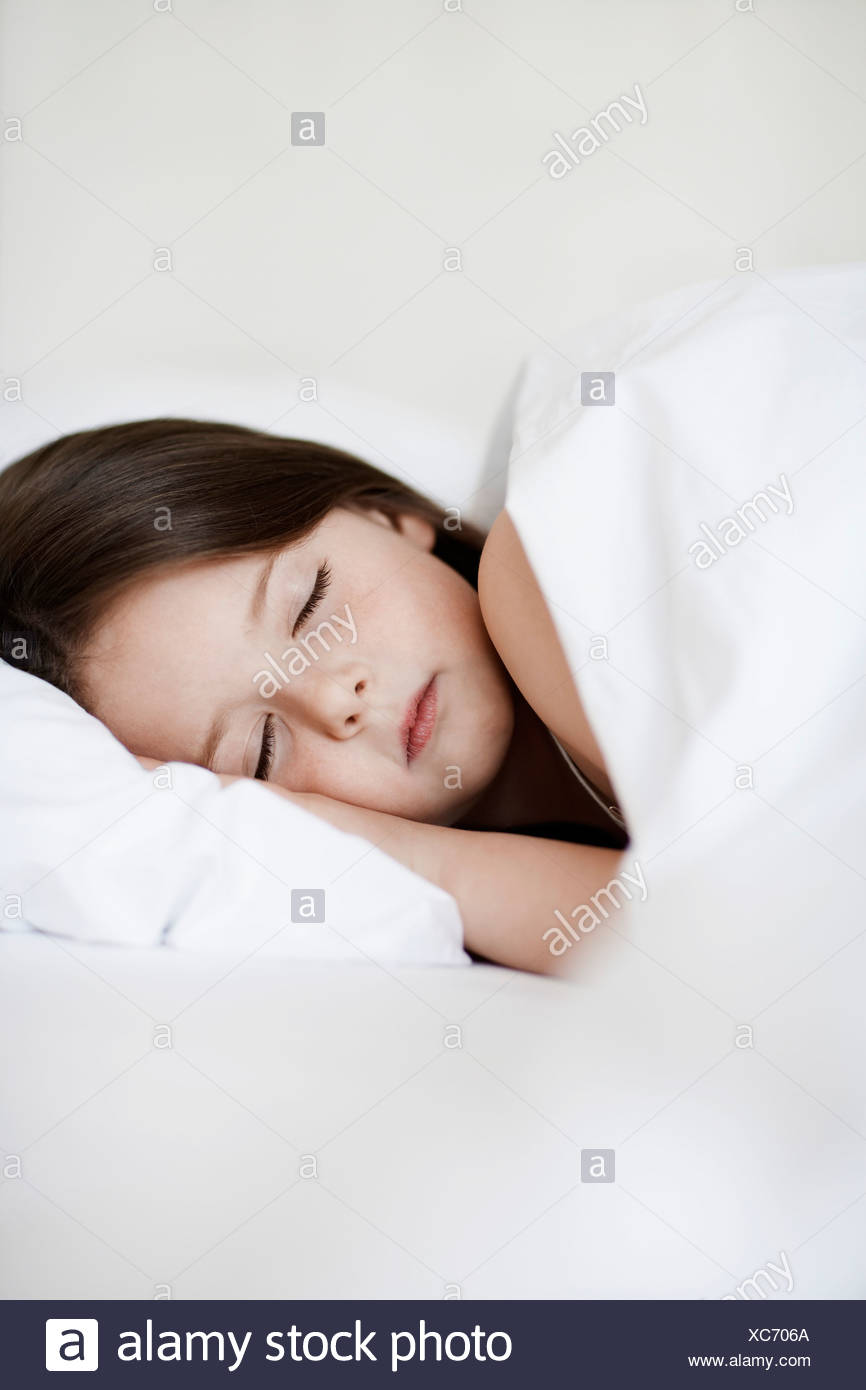 Little Girl Sleeping in bed, close up - Stock Image