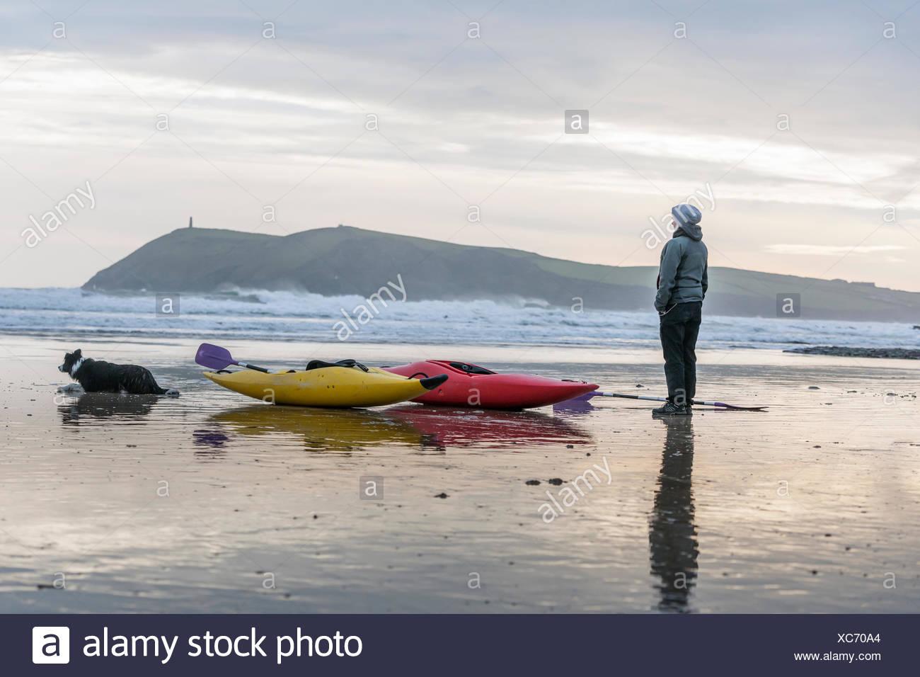 Young woman on beach with sea kayaks, Polzeath, Cornwall, England - Stock Image