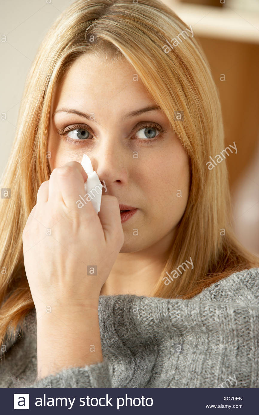 Young Woman With Cold Blowing Nose - Stock Image
