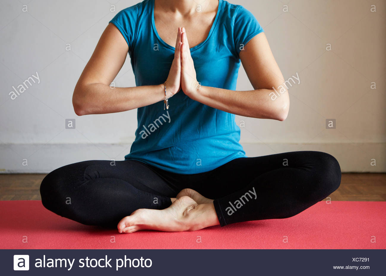 Cropped view of woman sitting cross legged, hands together meditating - Stock Image